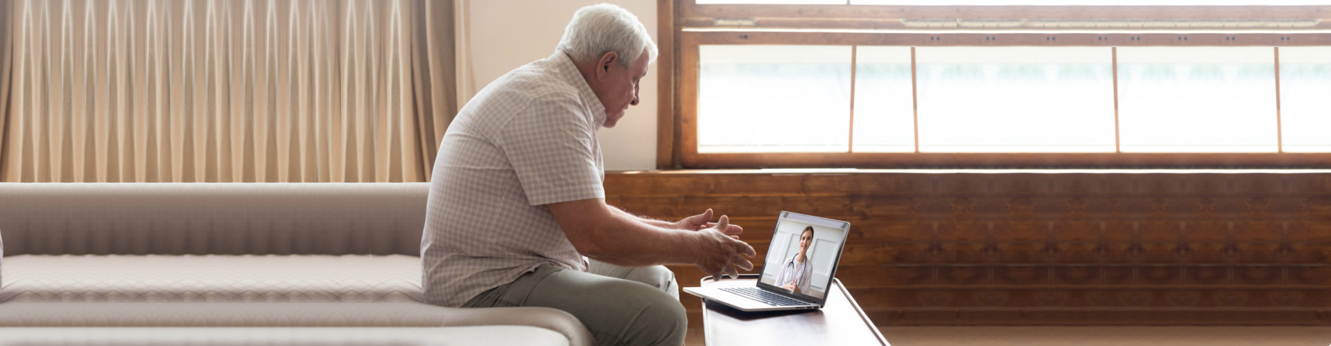 Elderly man sit on couch at home have online consultation on computer with female doctor or physician, mature grandfather patient consult do checkup with nurse talk on video call use webcam on laptop